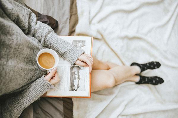 Bild zeigt Frau mit Tee Tasse und Buch in der Hand.